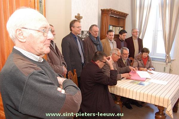 Pater Sus kijkt vanaan de zijlijn toe bij het ondertekenen van het contract.