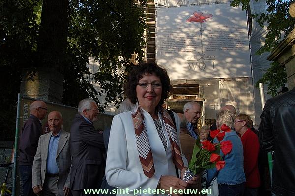 kunstenares Monik Thibaut voor het werfzeil van haar hand aan de Sint-Pieterskerk